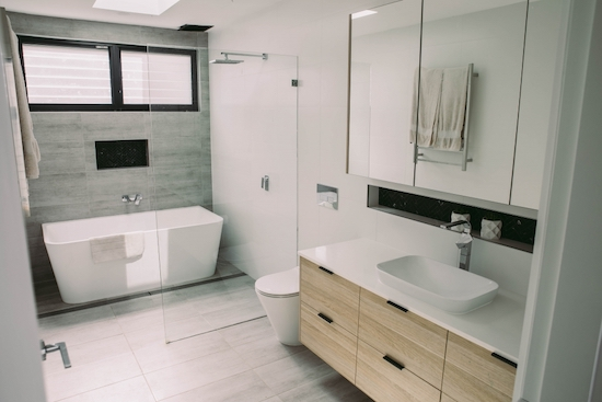 A modern bathroom with grey floor tiles, a white bathrub at the end of the room and behind the shower