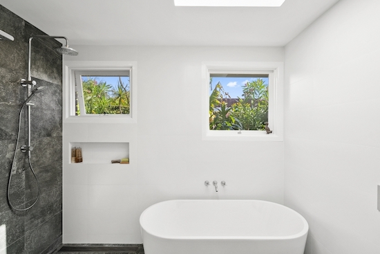 Bright, modern bathroom with a white bathtub in the middle and the shower are with dark grey wall tiles on the left