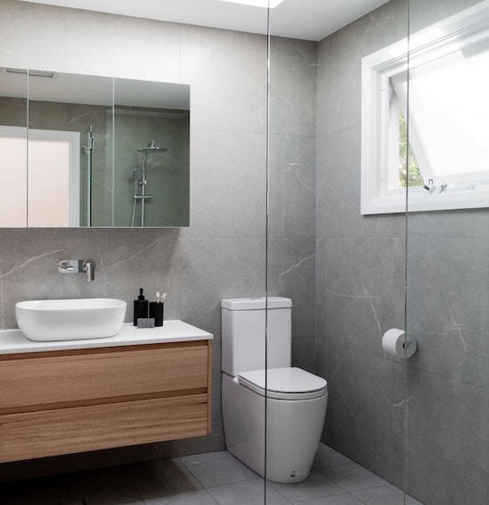 Renovated bathroom with big grey tiles, a timber vanity and a wall mirror